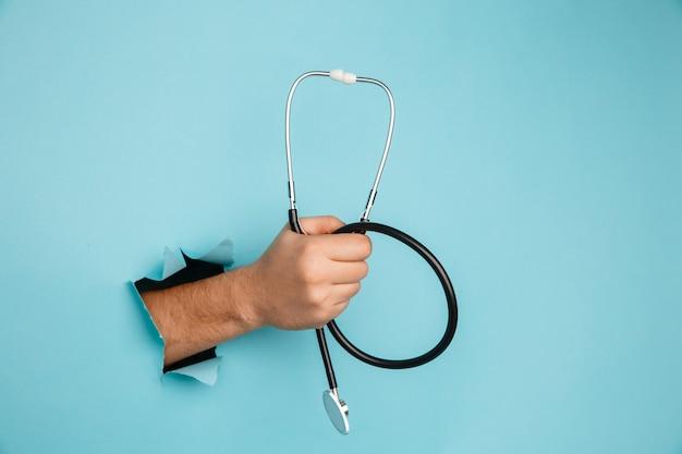 Estetoscópio na mão masculina sobre um fundo azul com um buraco, conceito médico.
