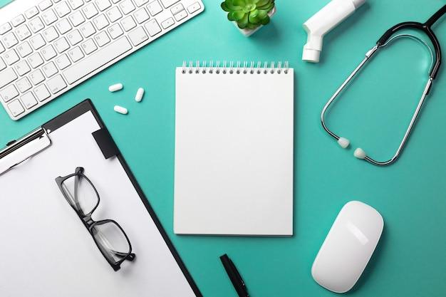 Estetoscópio na mesa de médicos com caderno, caneta, teclado, mouse e pílulas