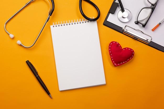 Estetoscópio na mesa de médicos com notebook e coração