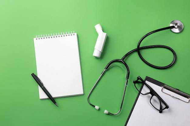 Estetoscópio na mesa de médicos com notebook e inalador