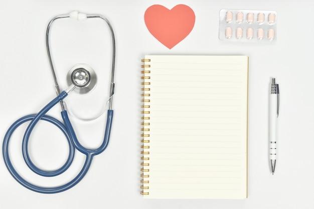 Estetoscópio na mesa de médicos com notebook e medicamentos.