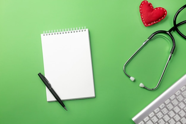 Estetoscópio na mesa de médicos com notebook, teclado e coração