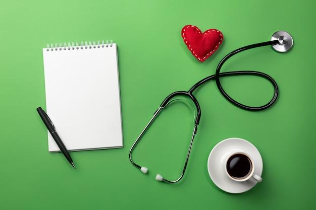 Estetoscópio na mesa de médicos com notebook, xícara de café e coração