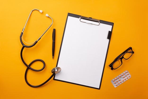 Estetoscópio na mesa de médicos com tablet, caneta e comprimidos