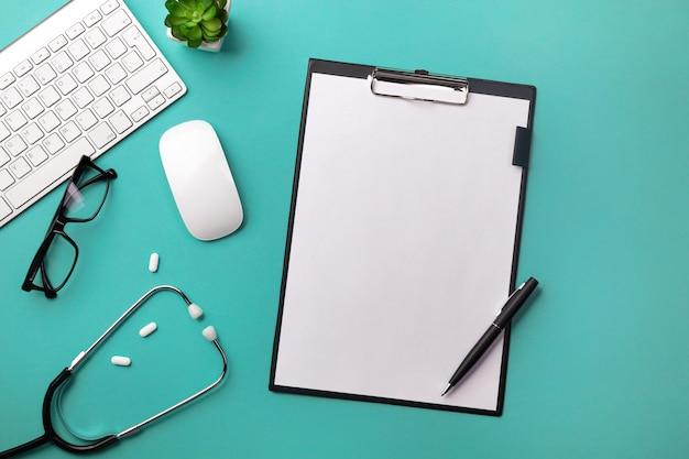 Estetoscópio na mesa de médicos com tablet, caneta, teclado, mouse e pílulas