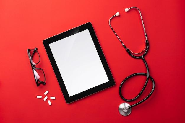 Estetoscópio na mesa de médicos com tablet digital e comprimidos
