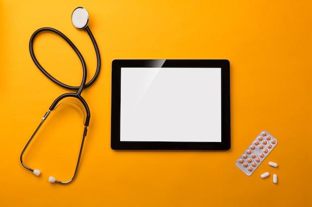 Estetoscópio na mesa de médicos com tablet digital e pílulas