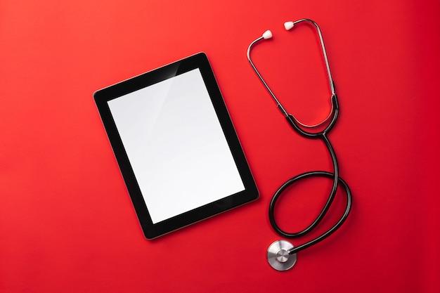 Estetoscópio na mesa de médicos com tablet digital, vista superior