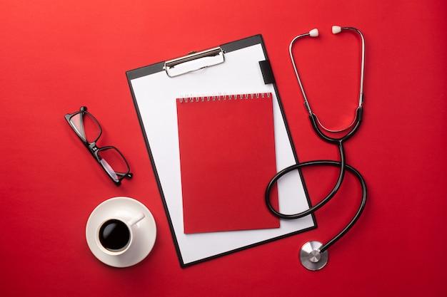 Estetoscópio na mesa de médicos com tablet e xícara de café, vista superior