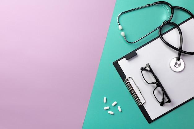 Estetoscópio na mesa de médicos com tablet, óculos e pílulas