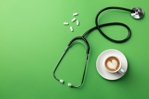 Estetoscópio na mesa de médicos com xícara de café e pílulas