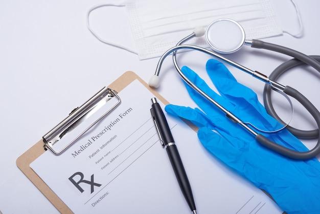 Estetoscópio na mesa dos médicos, conceito médico. coronavírus (covid-19. estetoscópio, óculos e máscara facial na mesa branca. proteção contra vírus, coronavírus, gripes, resfriados, doenças. vista de cima plana