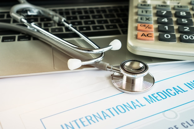 Estetoscópio no computador com seguro médico internacional