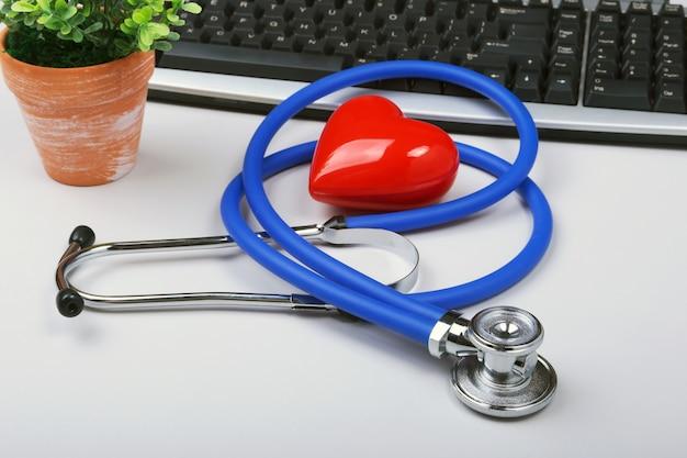 Estetoscópio no computador portátil moderno. coração vermelho na mesa branca com espaço para texto
