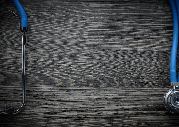 Estetoscópio no conceito de remédio de placa de madeira vintage