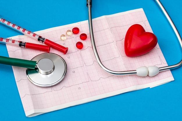 Estetoscópio no eletrocardiograma com comprimidos e seringa em fundo azul
