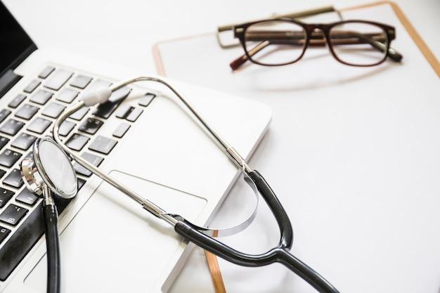 Estetoscópio no laptop com prancheta e óculos