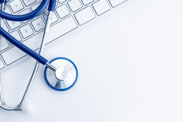 Estetoscópio no teclado do computador na mesa branca. conceito de cuidados de saúde ou telemedicina online. formação médica. vista do topo. copie o espaço