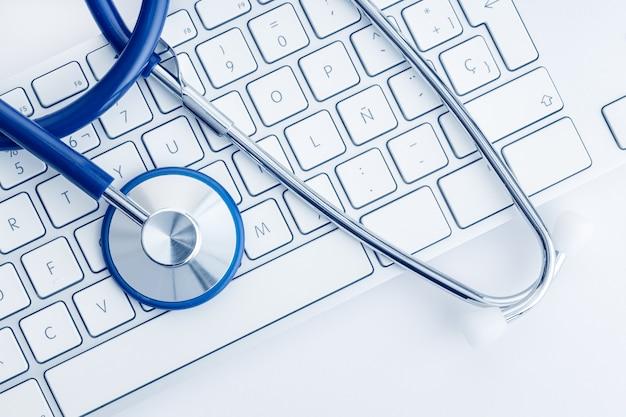 Estetoscópio no teclado do computador na mesa branca. conceito de cuidados de saúde ou telemedicina online. formação médica. vista do topo