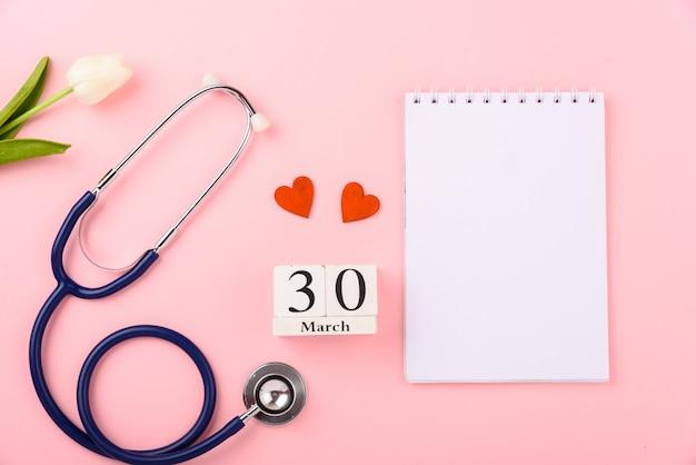 Estetoscópio, nota de papel, calendário, corações vermelhos e flor tulipa