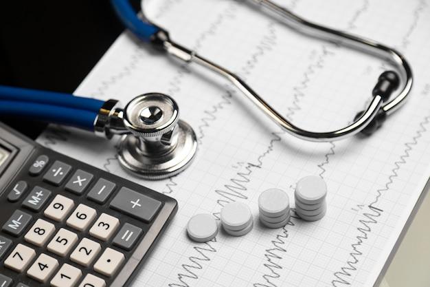 Estetoscópio, pílulas e calculadora estão em uma folha com um eletrocardiograma