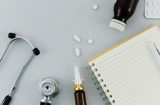 Estetoscópio; pílulas; garrafa; spray nasal; diário e caneta em fundo cinza