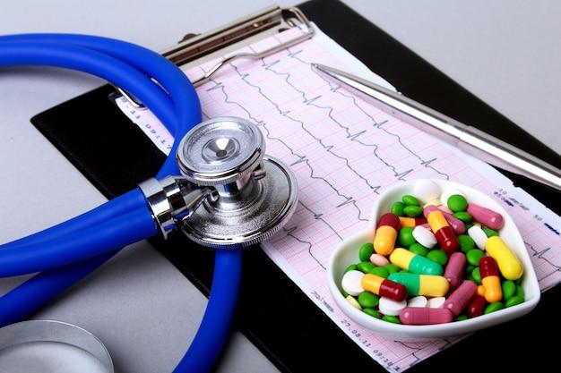 Estetoscópio, prescrição de rx e comprimidos e cápsulas coloridos da variedade na placa.