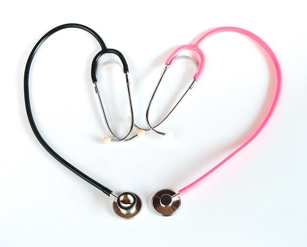 Estetoscópio preto e estetoscópio rosa fazendo um formato de coração em fundo branco.