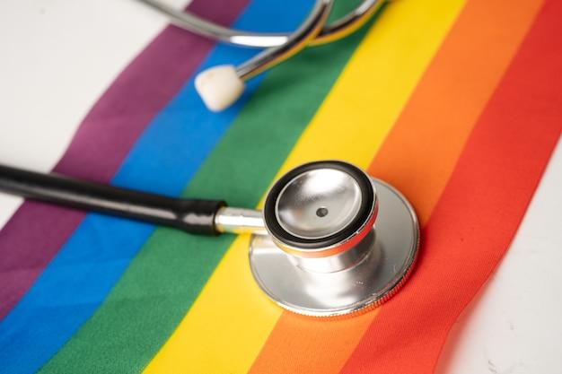 Estetoscópio preto na bandeira do arco-íris, símbolo do mês do orgulho lgbt