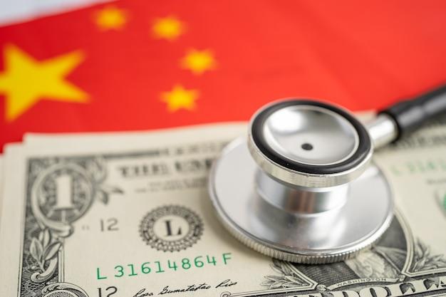 Estetoscópio preto no fundo da bandeira da china com notas de dólar americano, negócios e conceito de finanças.