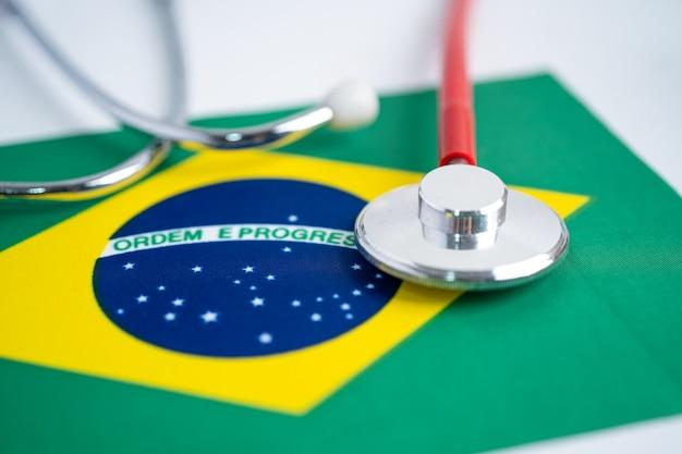Estetoscópio preto sobre fundo de bandeira do brasil, conceito de negócios e finanças.
