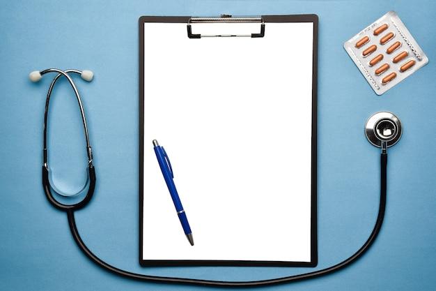 Estetoscópio, quadro branco, caneta e blister com comprimidos encontram-se sobre um fundo azul