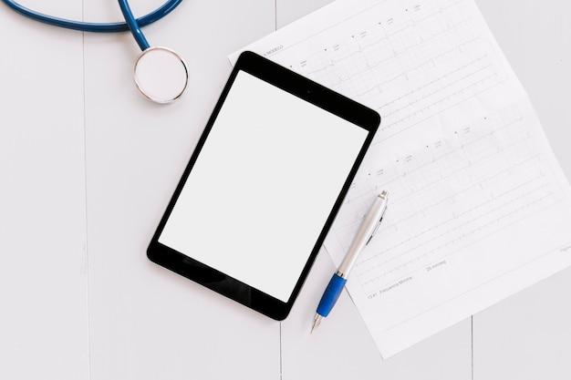 Estetoscópio; tablet digital; gráfico de caneta e eletrocardiograma na superfície de madeira branca
