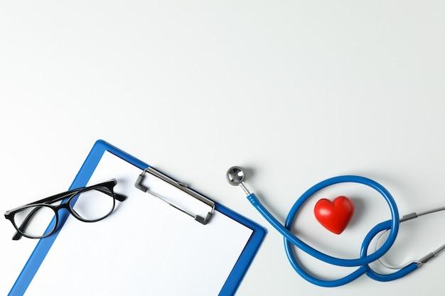Estetoscópio, tablet e coração em fundo branco, espaço para texto