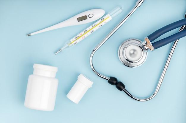 Estetoscópio, termômetro e pílulas.