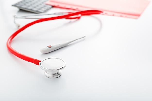 Estetoscópio termômetro médico vermelho na mesa branca. equipamento profissional de médicos no espaço de trabalho.