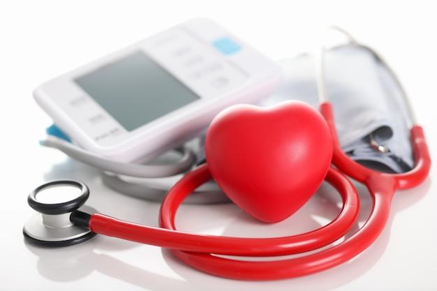 Estetoscópio tonômetro automático e pequeno coração vermelho na mesa