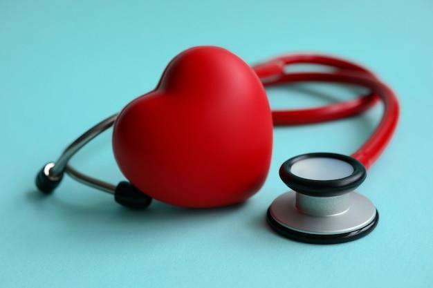Estetoscópio vermelho com coração no fundo azul moderno