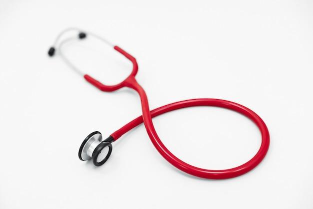 Estetoscópio vermelho encontra-se em uma superfície branca, um dispositivo para ouvir sons de órgãos
