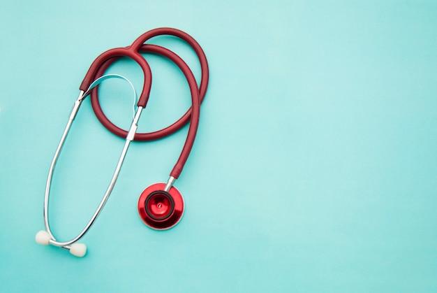 Estetoscópio vermelho médico isolado em azul. copyspace. cuidados de saúde e medicina.