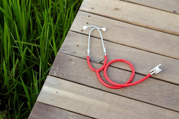 Estetoscópio vermelho na madeira ao ar livre