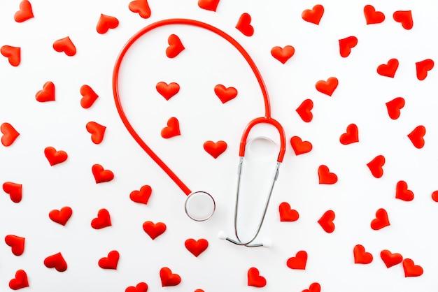 Estetoscópio vermelho, rodeado de corações, visto de cima isolado no branco