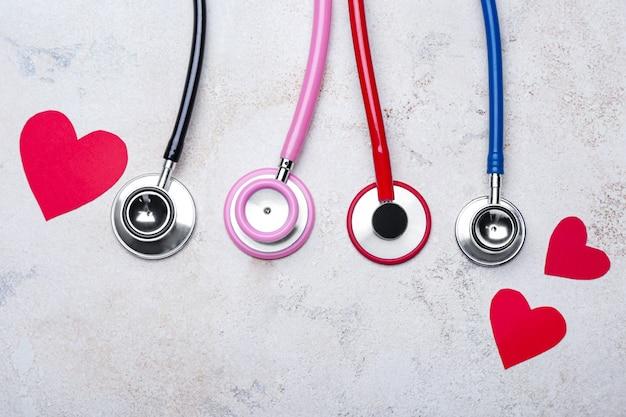 Estetoscópios e corações em cinza. conceito de cardiologia