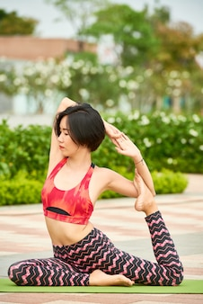 Esticando a mulher no tapete de ioga ao ar livre