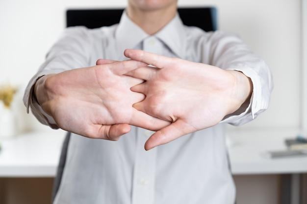 Esticando os braços no local de trabalho do escritório escasso. mãos de um funcionário na frente da área de trabalho moderna, conceito de trabalho realizado