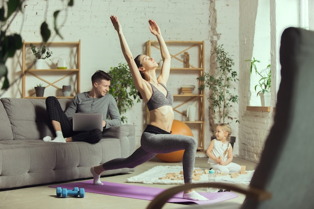 Esticando-se na frente do sofá. jovem mulher exercitando fitness, aeróbica, ioga em casa, estilo de vida esportivo e ginástica em casa.