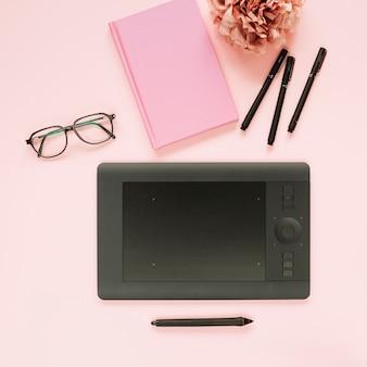 Estilete e tablet digital gráfico com artigos de papelaria no fundo rosa