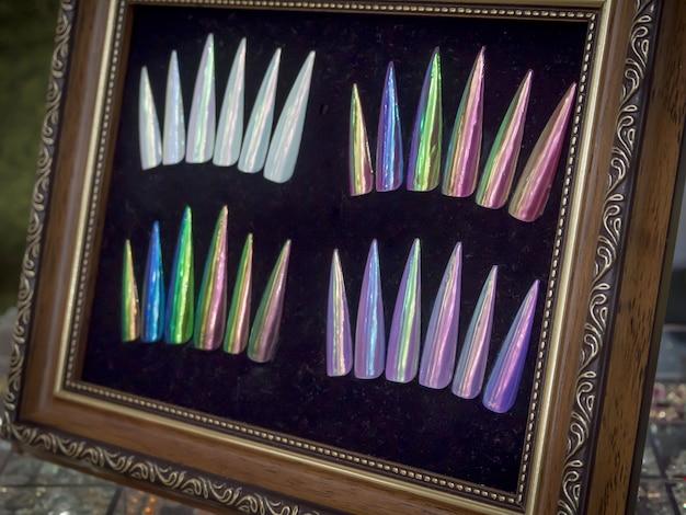 Estiletes com pontas multicoloridas cobertos com vernizes brilhantes