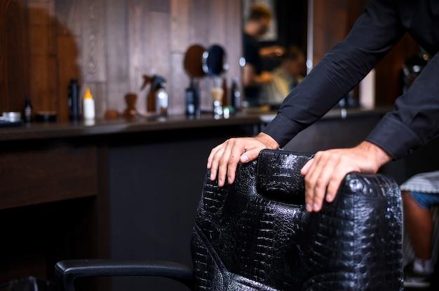 Estilista, apoiando-se na cadeira de couro de barbearia
