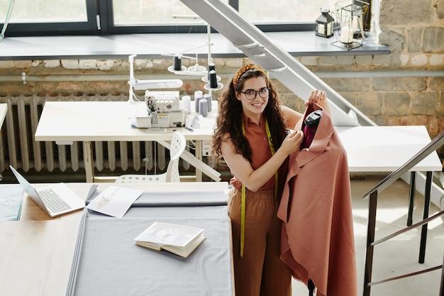 Estilista bonita trabalhando em uma nova coleção sazonal de casacos em seu estúdio ou oficina, ao lado de um manequim